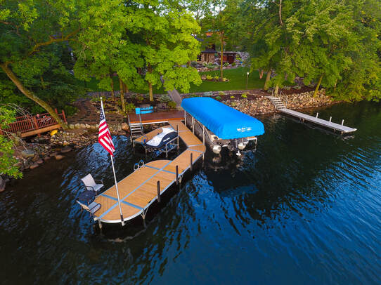 Lake Area Docks & Lifts ShoreMaster RS4 sectional dock with wood grain aluminum (Cedar look) decking, vertical bumpers, DVS vertical lift with blue canopy, PWC Lift, and american flag